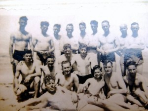 Ken and comrades, showing off their muscles in desert sun. I think he is 4th from right standing.