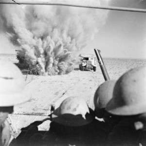 El Alamein: A mine explodes close to a British truck as it carries infantry through enemy minefields and wire to the new front lines.
