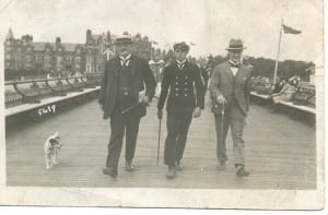 The young Reg looks dapper in his Merchant Navy uniform, carrying a baton and smoking a cigarette from the corner of his mouth, like his father William on the left. On the right, with a brolly, is his Uncle Alf. As his father is wearing a straw boater, they seem to be on holiday, striding along a wooden pier with women in white hats and a hotel in the background.
