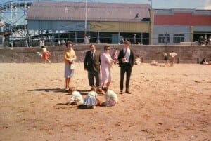 Reg and Thelma (centre), with Peggy and John Dale on the beach outside Wonderland, Cleethorpes, watch family members build sandcastles. Men wear ties. Note the wooden roller coaster, long demolished, where John had holiday work
