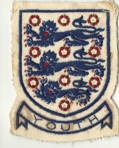 John's England badge bearing the Three Lions.